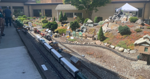 Railroad moving through a miniature garden railroad