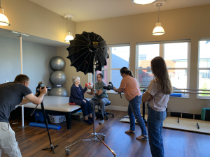 Camera crew taking photos of a woman lifting weights with a trainer for a senior living photo shoot.