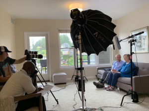 Behind the scenes of a husband and wife being interviewed with cameras and lighting equipment in front of them.