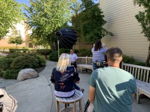 Looking over the shoulder of the cameraman during an interview of a man sitting on a bench during a senior living photo shoot.